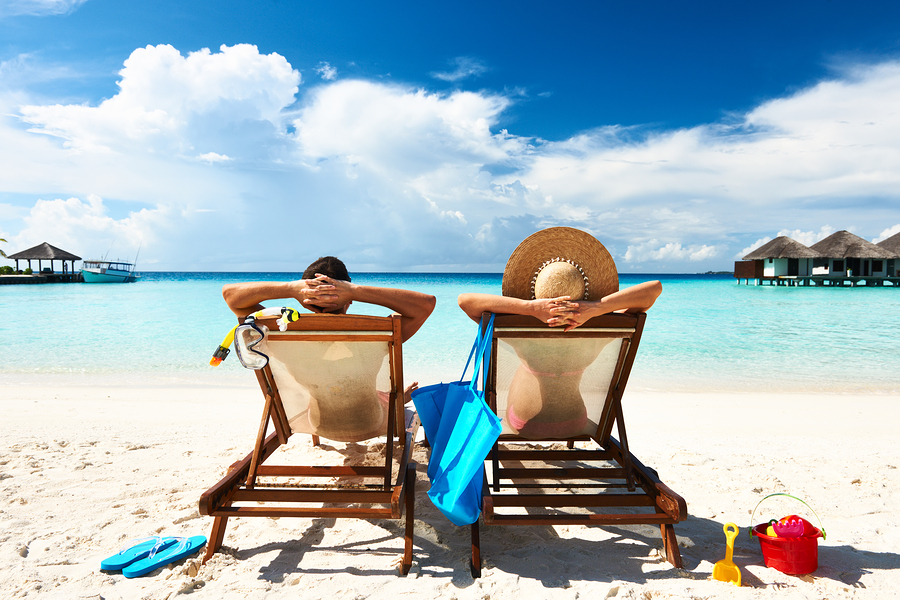 Two people on a holiday at the beach, plan your finances before buying stock, property, investments