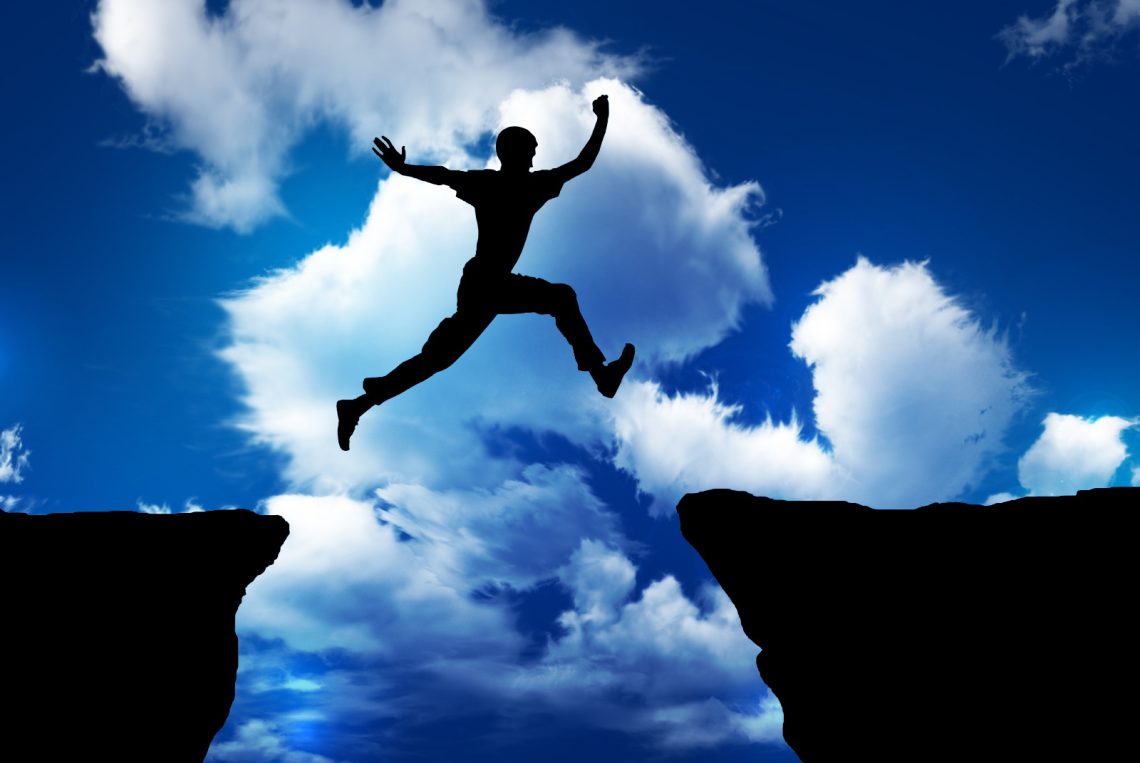 man confidently jumping between two cliff edges. Describes confidence with investment decisions, or over confidence